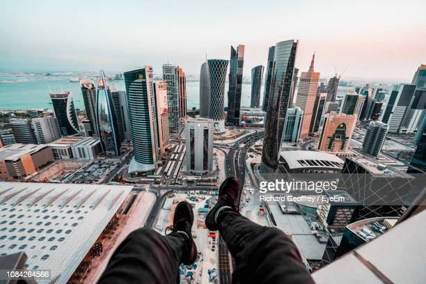 low section of man sitting on terrace against cityscape - katar stock-fotos und bilder