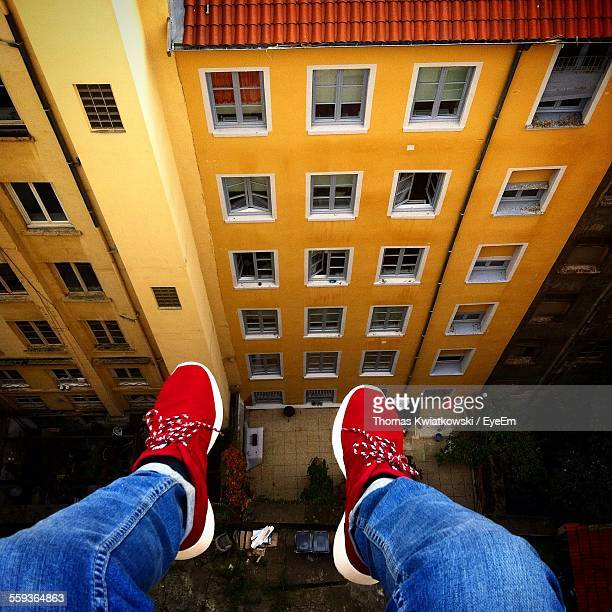 Low Section Of Man Sitting On Top Of Building Terrace