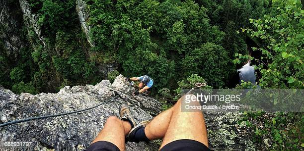 Low Section Of Man Sitting On Top While Person Climbing Mountain
