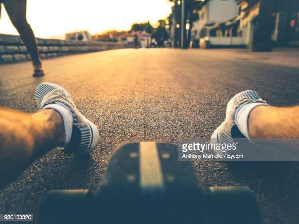 Low Section Of Man Sitting With Skateboard On Road