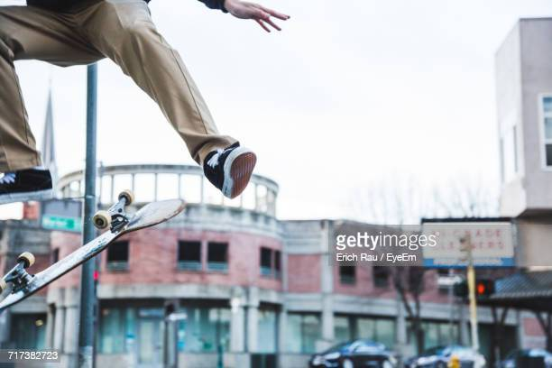 Low Section Of Man Skateboarding Against Clear Sky