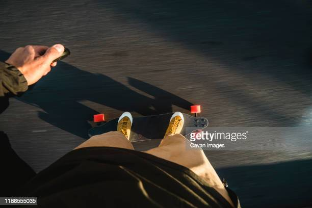 low section of man skateboarding on road in city - perspectiva personal fotografías e imágenes de stock