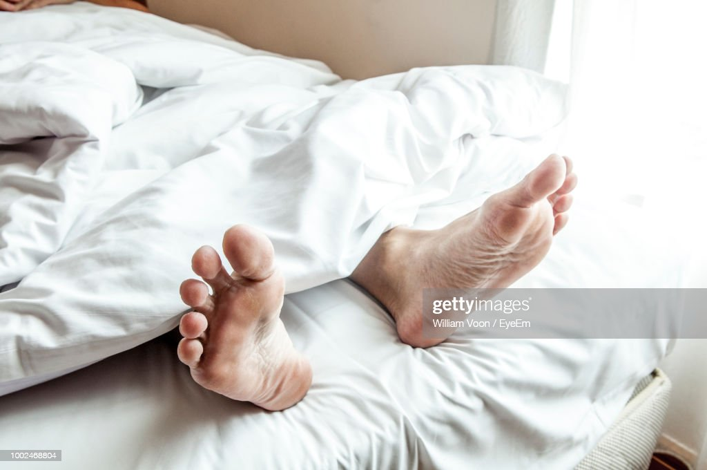 Low Section Of Man Sleeping On Bed At Home : Stock Photo