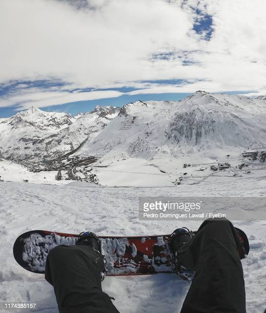 low section of man snowboarding on mountain against cloudy sky - snowboarding stock pictures, royalty-free photos & images