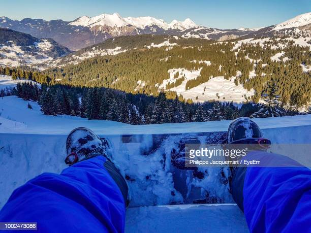 Low Section Of Man Snowboarding On Ski Slope
