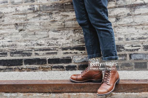 low section of man standing against brick wall - brown shoe stock pictures, royalty-free photos & images