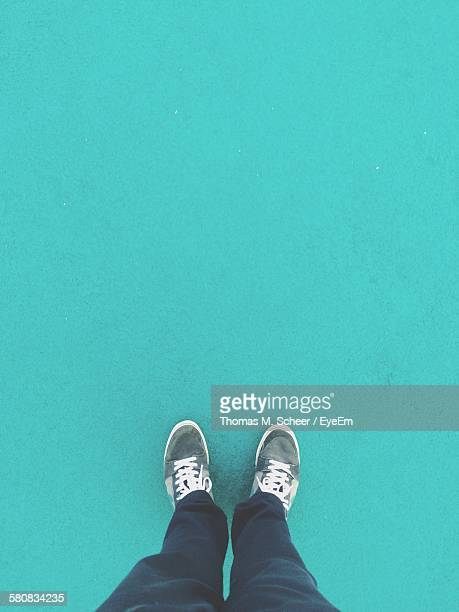 low section of man standing against turquoise background - blue shoe stock pictures, royalty-free photos & images