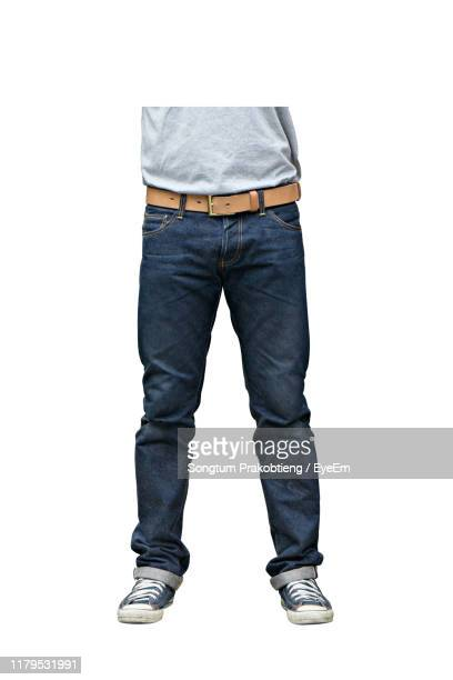low section of man standing against white background - spijkerbroek stockfoto's en -beelden