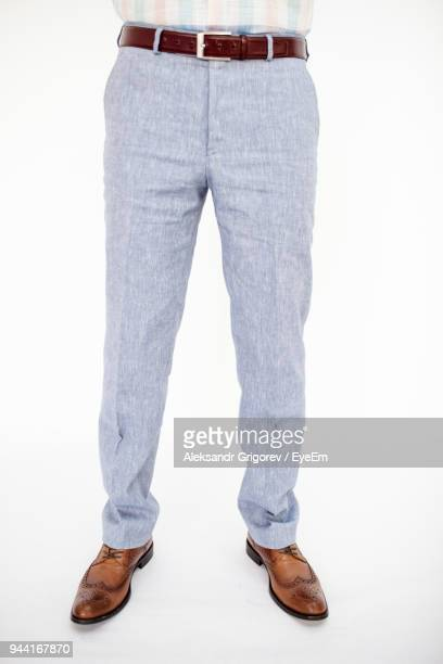 low section of man standing against white background - pantalón fotografías e imágenes de stock