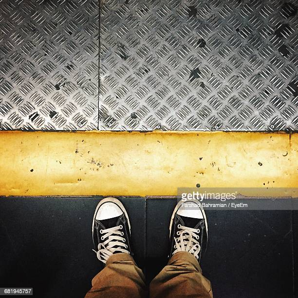 Low Section Of Man Standing Against Yellow Line At Subway Station