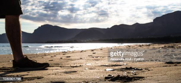 Low Section Of Man Standing At Beach Against Cloudy Sky