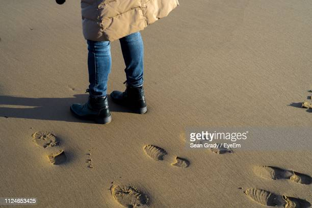low section of man standing at beach - shoe print stock pictures, royalty-free photos & images
