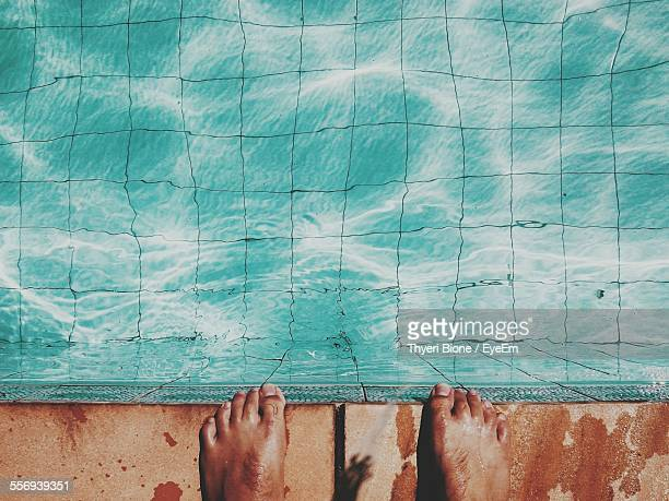 Low Section Of Man Standing At The Edge Of Swimming Pool