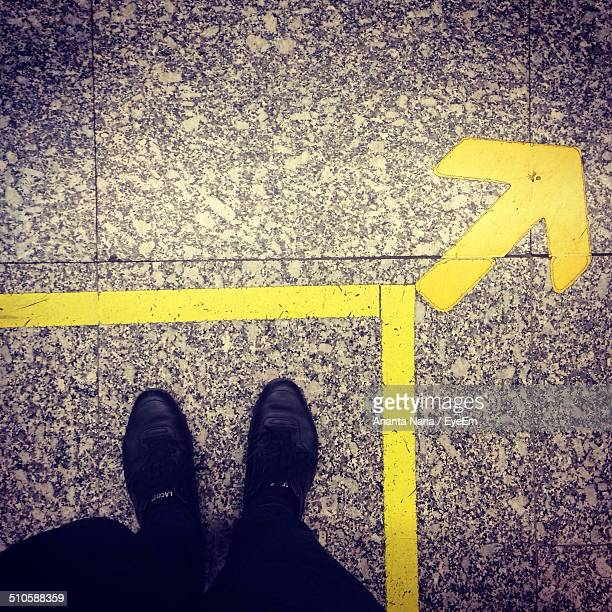Low section of man standing by arrow sign