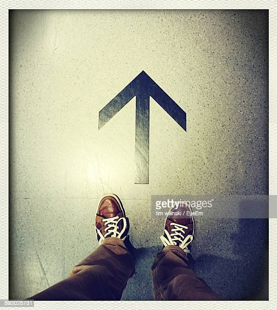 Low Section Of Man Standing By Arrow Symbol On Floor