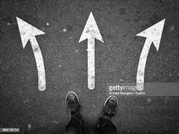 low section of man standing by arrow symbols on road - richtung stock-fotos und bilder