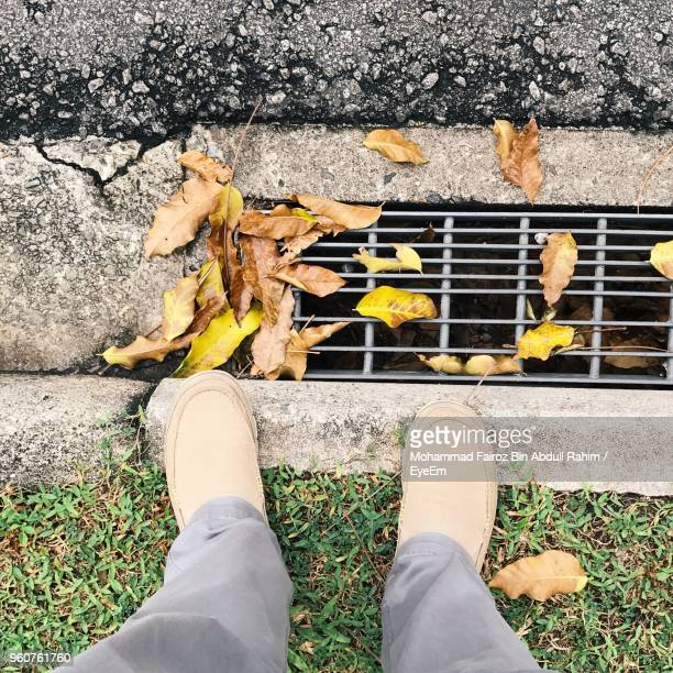 Low Section Of Man Standing By Autumn Leaves On Sewer