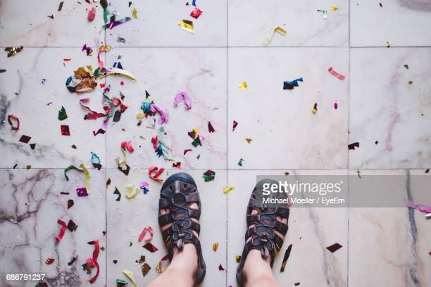 low section of man standing by confetti on tiled floor - konfetti boden stock-fotos und bilder
