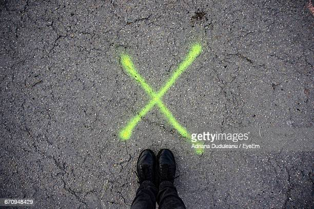 low section of man standing by cross mark on street - low section stock pictures, royalty-free photos & images