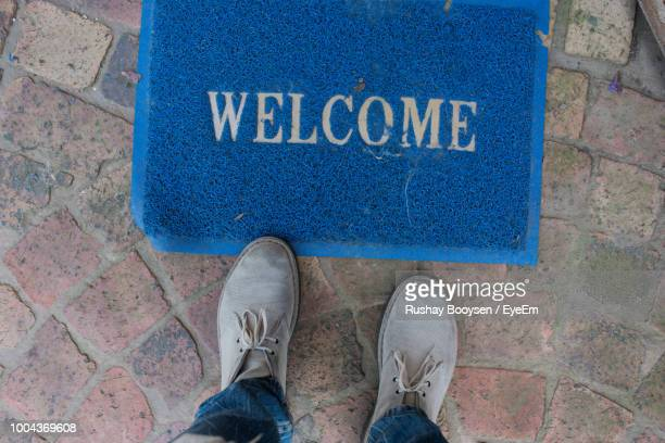 Low Section Of Man Standing By Doormat