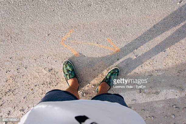 Low Section Of Man Standing By Double Arrow Symbol On Road