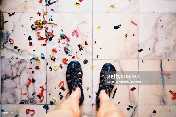 Low Section Of Man Standing By Fallen Confetti On Tiled Floor