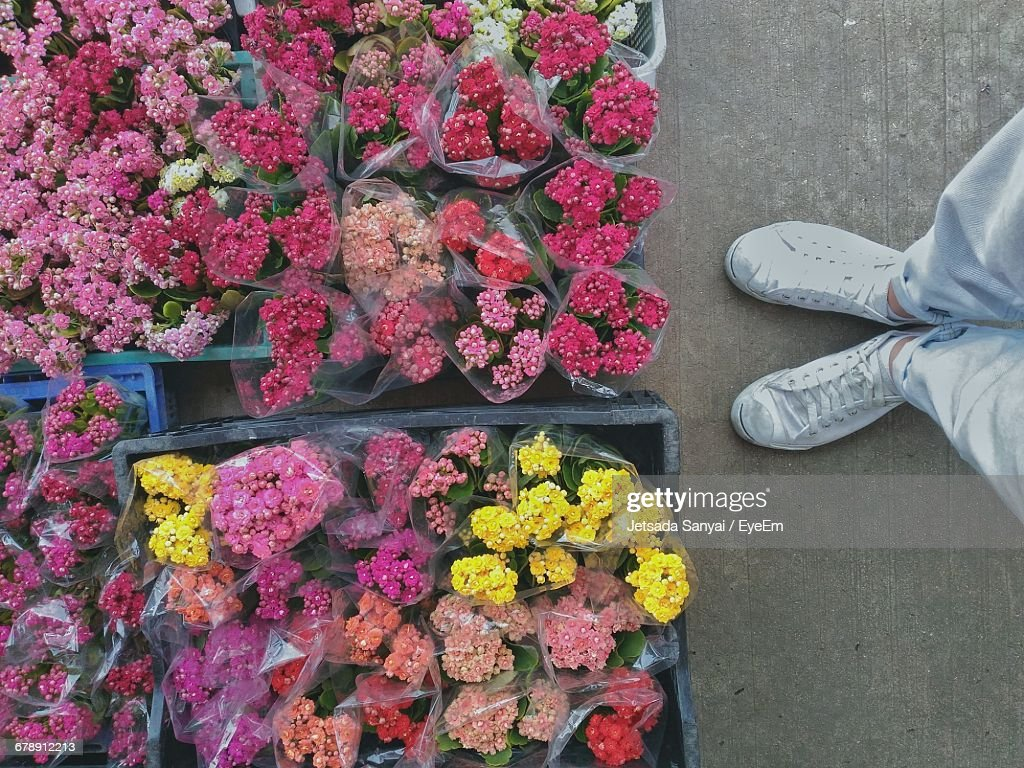 Low section of man standing by flower bouquets in crate at market low section of man standing by flower bouquets in crate at market stall stock photo izmirmasajfo