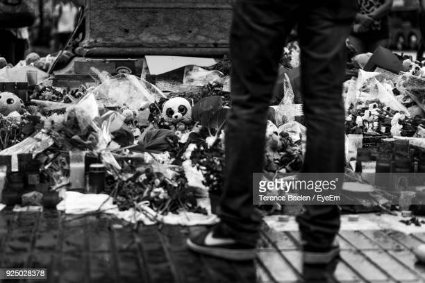 low section of man standing by flowers at cemetery - terrorism stock pictures, royalty-free photos & images