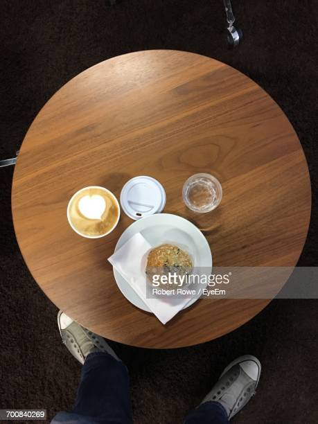 Low Section Of Man Standing By Food And Cappuccino On Table