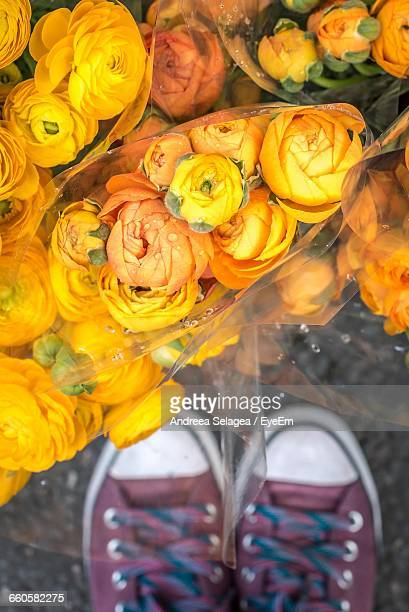 Low Section Of Man Standing By Fresh Yellow Roses Bouquets At Market Stall