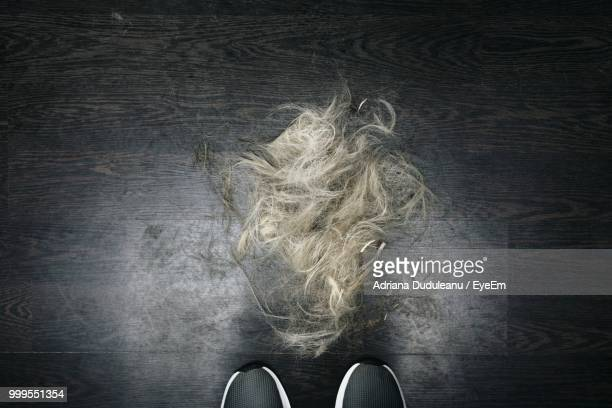 low section of man standing by hair on floor - low section stock pictures, royalty-free photos & images