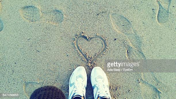 Low Section Of Man Standing By Heart Shape On Beach