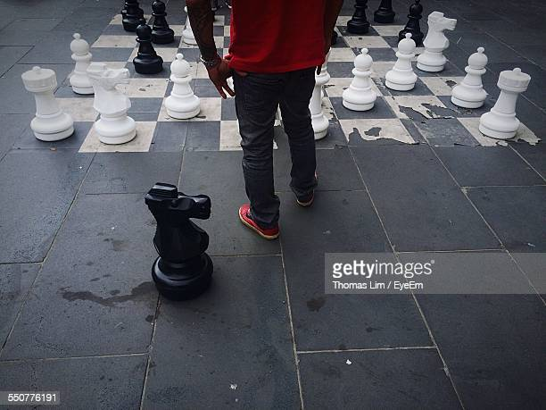 Low Section Of Man Standing By Large Chess In City
