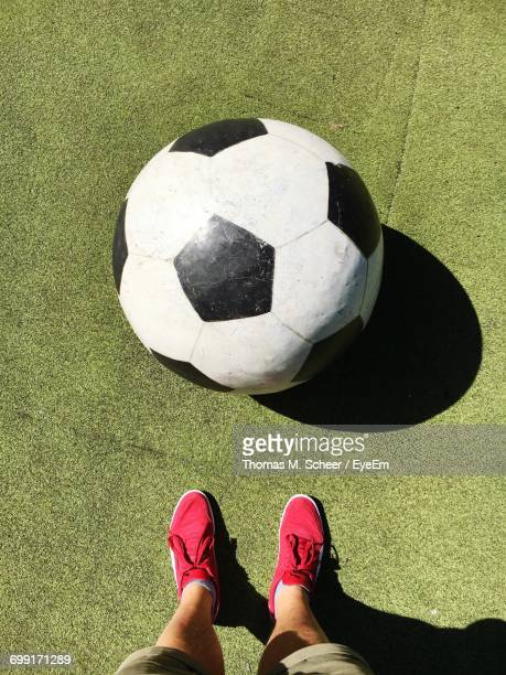 Low Section Of Man Standing By Large Soccer Ball On Field