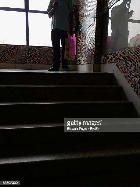 Low Section Of Man Standing By Staircase
