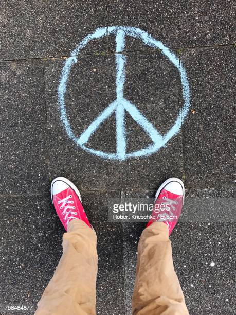 Low Section Of Man Standing By Symbols Of Peace Logo On Footpath