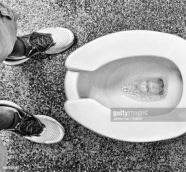 low section of man standing by toilet seat in bathroom - grooming product stock photos and pictures