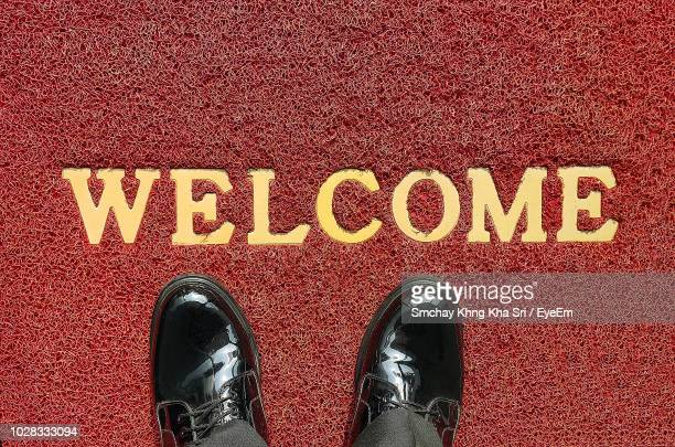 low section of man standing by welcome sign on doormat - human doormat foto e immagini stock