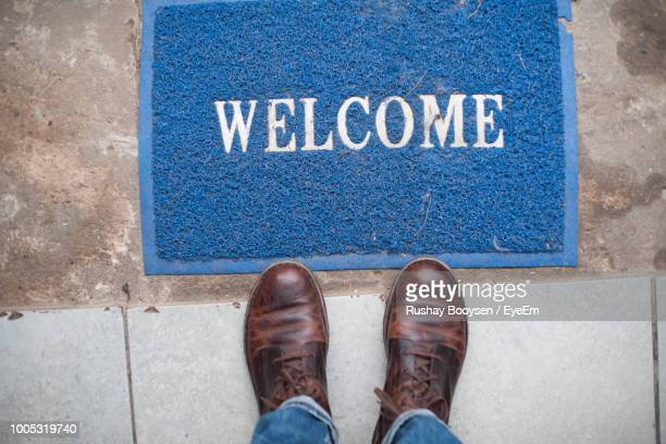 low section of man standing by welcome text on doormat - human doormat foto e immagini stock