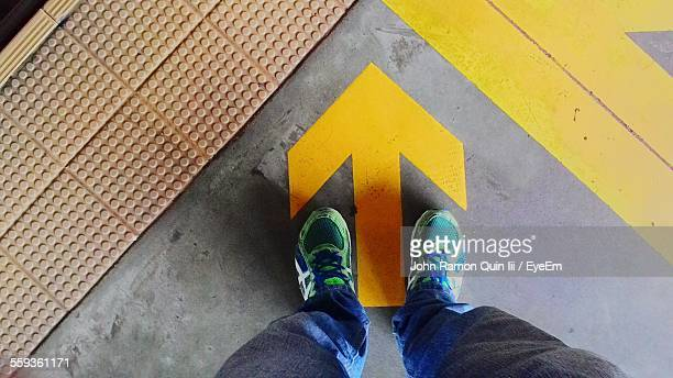 low section of man standing by yellow arrow sign - guidance stock pictures, royalty-free photos & images