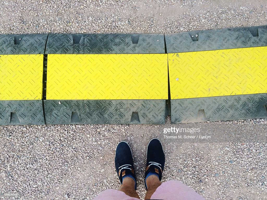 Low Section Of Man Standing By Yellow Line On Road Marking : Stock Photo