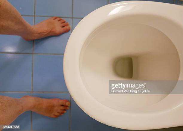 low section of man standing in front of toilet bowl in bathroom - toilet bowl stock photos and pictures