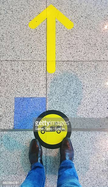 low section of man standing in front of vehicle sign at dubai international airport - arab feet photos et images de collection
