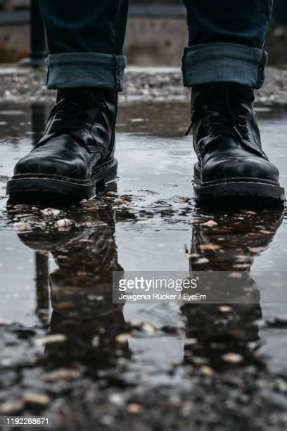low section of man standing in puddle - black boot stock pictures, royalty-free photos & images