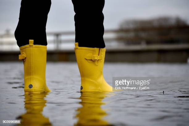 low section of man standing in puddle - rubber boot stock pictures, royalty-free photos & images