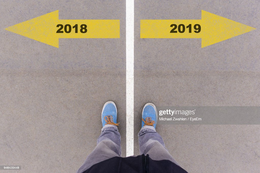 Low Section Of Man Standing On Arrow Sign : Stock Photo