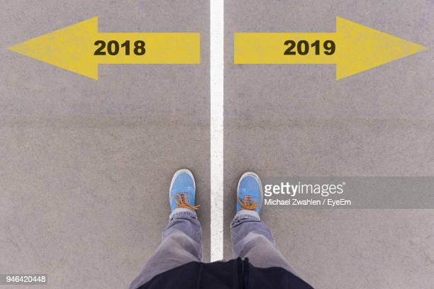 low section of man standing on arrow sign - 2019 stock pictures, royalty-free photos & images
