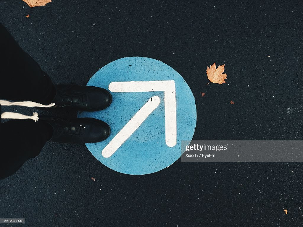 Low Section Of Man Standing On Arrow Symbol : Stock Photo