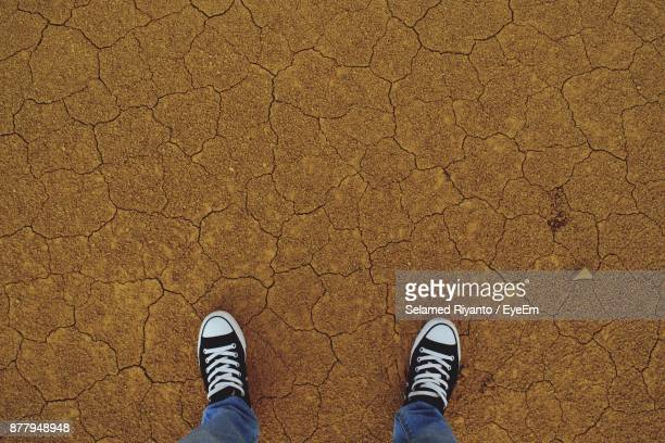 Low Section Of Man Standing On Barren Landscape