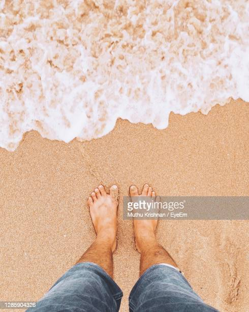 low section of man standing on beach - sand stock pictures, royalty-free photos & images